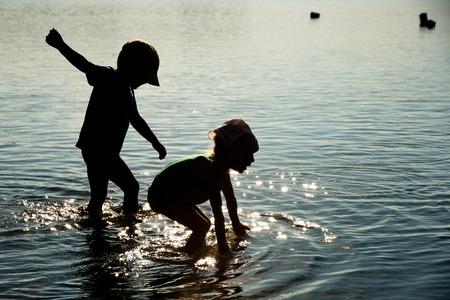 ni�as jugando: Ni�os jugando en el agua Foto de archivo