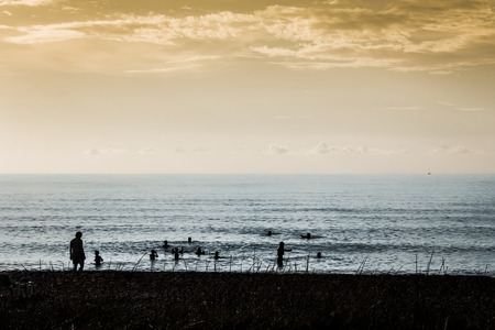 Silhouettes of people enjoying vacation on the beach photo