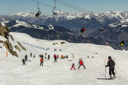 snow grooming machine: Skiing people, the chair lifts and rope tow systems of Kaprun ski region in Austria Stock Photo