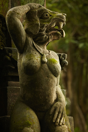 antiquities: One of the Balinese spirit statues with dog head and woman body Stock Photo