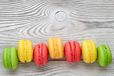 colorful macarons over   wood table. top view