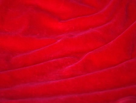 background of red velvet fabric with a wavy soft folds photo