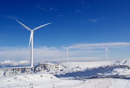 power in nature turbine: Three windmills to generate electricity on a snowy mountain Stock Photo