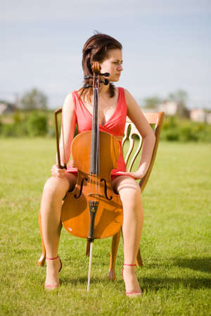 girl with the violin siting on the chair photo
