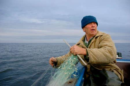 pescador: viejo pescador de pesca en el mar (en barco)