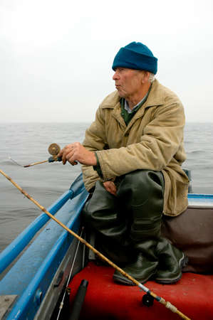 old fisherman fishing on the sea (in boat)