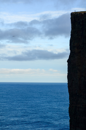 A person standing on the edge of a high cliff on Faroe Islands