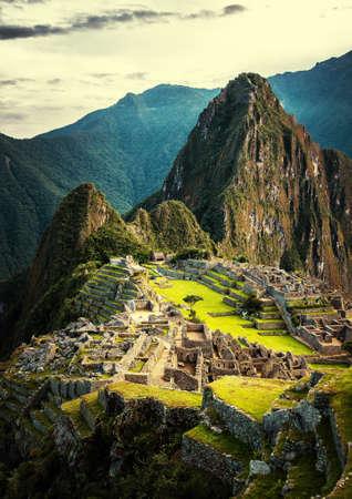 Machu Picchu bei Sonnenuntergang, wenn die Sonne macht alles golden-warm. Sonnenuntergang am Machu Picchu, Peru. Berg Huayna Picchu Anstieg über Inka-Ruinen von Machu Picchu - Sacred Valley.