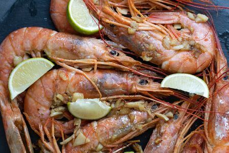 fried langoustine with lime and garlic on a black plate Banque d'images