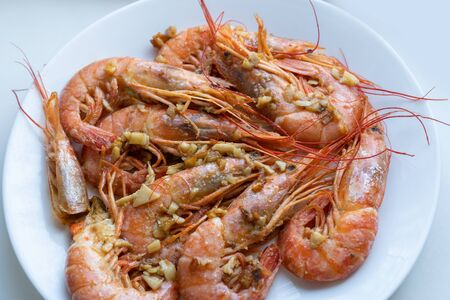 fried prawns with lime and garlic on a white plate