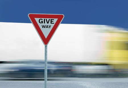 give way: Give way yield road traffic sign and truck in the background Stock Photo