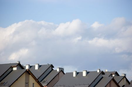 Rowhouse roofs and a cloudscape photo