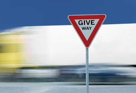 Give way yield road traffic sign with text and truck in the background photo