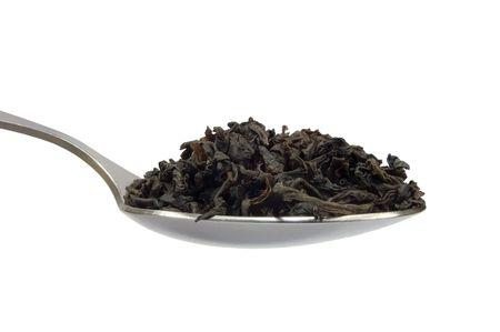 assam tea: Teaspoon with tea leaf, isolated macro closeup