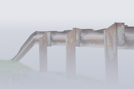 Old aged rusty grunge metallic bridge rail, shoruded in mist Stock Photo - 7498318