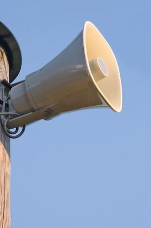 spl: grey plastic horn loudspeaker on the pole, over blue sky