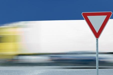 ceda: Se�al de tr�fico de carretera de rendimiento de manera de dar y cami�n borrosa de movimiento en segundo plano