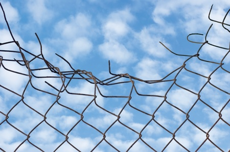 Grynge aged crushed rusty wire security fence, over cloudscape, skies, clouds and sky
