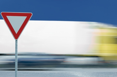 Give way yield road traffic sign and motion blurred truck in the background photo
