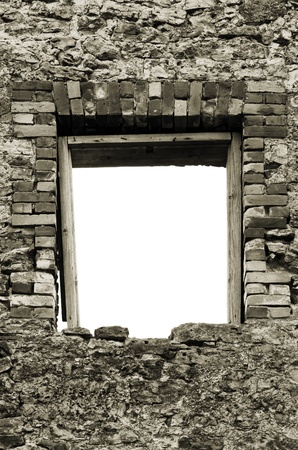 Ruined rustic limestone boulder rubble wall masonry stonework ruins and empty blank isolated red brick window aperture opening with weathered old aged wooden frame in bw sepia photo