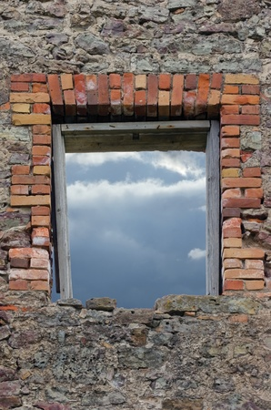 Ruined rustic limestone boulder rubble wall masonry stonework ruins and red brick window aperture opening with weathered old aged wooden frame showing cloudy sky photo
