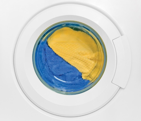 laundry detergent: Washing machine door, clean colorful clothes, yellow, blue plush terry Stock Photo