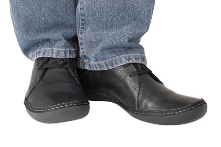 スニーカー: 黒革の靴、灰色のデニムのジーンズ、カジュアルな男性