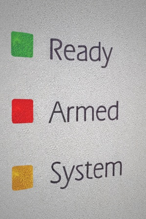 burgler: Armed home security alarm system panel macro closeup, green, red, yellow ready set signal lights Stock Photo