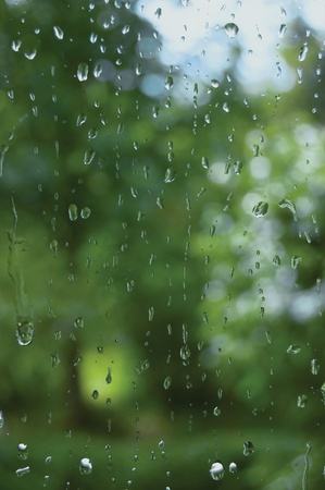 Rainy summer day, raindrops on window glass, macro closeup