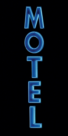 Blue Neon Motel sign, lit up at night, vertical isolated closeup photo
