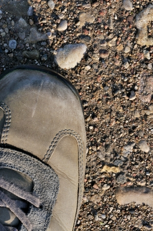 Hiking boot off-road shoe on hard arid dried soil, vertical close up, detailed macro of bare earth, dust, stones, rocks, pebbles, sand, ash photo