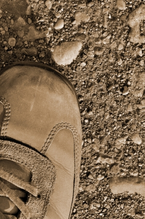Hiking boot off-road shoe on hard arid dried soil in sepia, vertical close up, detailed macro of bare earth, dust, stones, rocks, pebbles, sand, ash