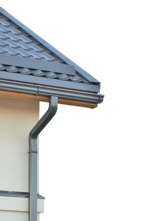 Brand nieuwe dakbedekking, grijs dak, geà ¯ soleerde grijze dakpannen, gedetailleerde constructie, beige gele muur en dakgoot closeup, verticaal kopie ruimte Stockfoto