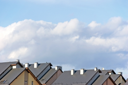 pitched roof: Row house roofs, condo rooftop panorama and bright summer cloudscape