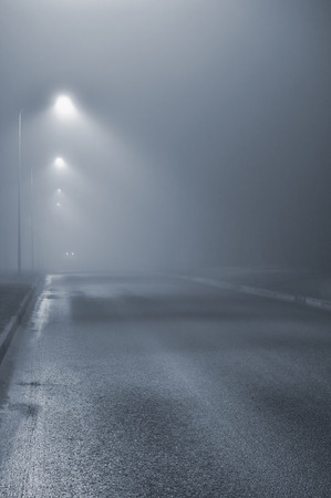 Street lights, foggy misty night, lamp post lanterns, deserted road in mist fog, wet asphalt tarmac, car headlights approaching, blue key