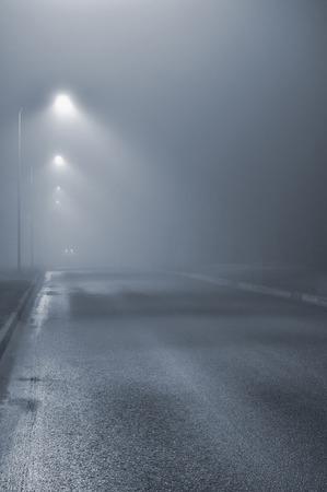 lamp posts: Street lights, foggy misty night, lamp post lanterns, deserted road in mist fog, wet asphalt tarmac, car headlights approaching, blue key
