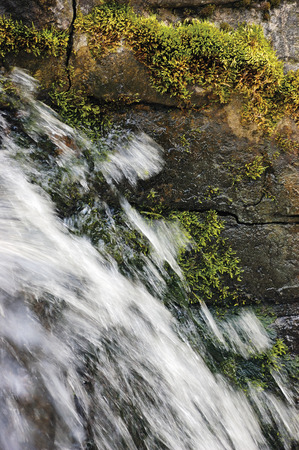 Running, water cascade waterfall streaming splashes, decorative granite stonewall background, green moss, grey rock stone wall, large detailed vertical masonry closeup bright white motion blurred drops texture pattern photo
