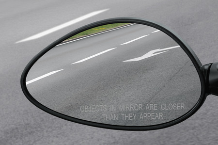 closer: Rear view mirror with warning text objects in mirror are closer than they appear, reflecting road, left side lateral, macro closeup, tarmac asphalt background reflection, white lines, arrows marking
