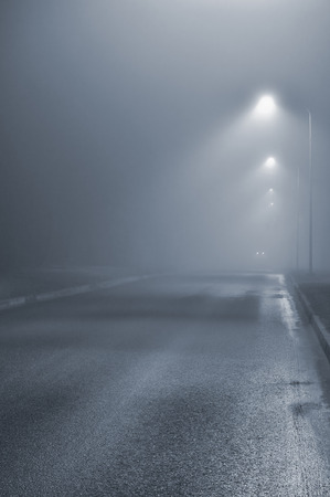 lamp light: Street lights, foggy misty night, lamp post lanterns, deserted road in mist fog, wet asphalt tarmac, car headlights approaching, blue key