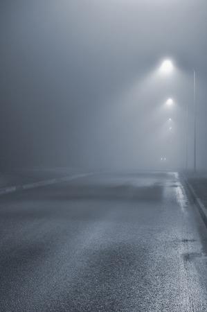 Street lights, foggy misty night, lamp post lanterns, deserted road in mist fog, wet asphalt tarmac, car headlights approaching, blue key