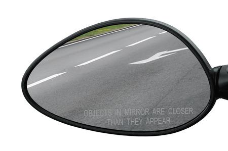 rear view mirror: Espejo retrovisor con objetos de texto de advertencia en el espejo est�n m�s cerca de lo que parecen, aislado, camino que refleja, lado izquierdo laterales, primer macro, asfalto asfalto reflexi�n, l�neas blancas, flechas marcando Foto de archivo