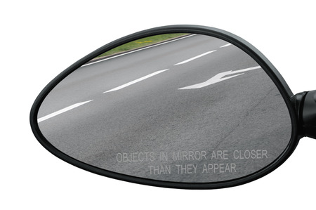 Rear view mirror with warning text objects in mirror are closer than they appear, isolated, reflecting road, left side lateral, macro closeup, tarmac asphalt reflection, white lines, arrows marking