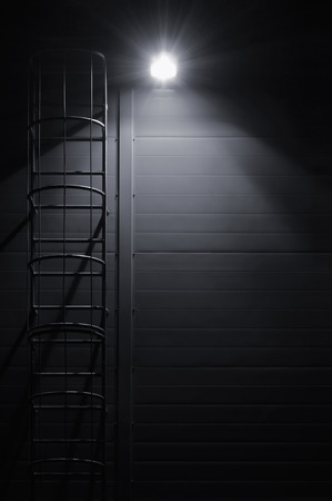 emergency stair: Fire emergency rescue access escape ladder stairway roof maintenance stairs at night bright shining lantern lamp light illumination glow shadows rustic textured industrial building wall panels texture pattern large detailed vertical closeup copy space bac Stock Photo