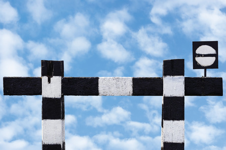 isolated sign: Dead end no through train railroad traffic sign, isolated weathered old grungy trains railway stop symbol signal signage, black and white striped retro barrier, large detailed closeup, blue bright cloudscape background, summer sky and white clouds pattern Stock Photo