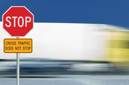 sign post: Red stop road sign, motion blurred truck vehicle traffic in background, regulatory warning signage octagon, white octagonal frame, metallic pole post, yellow cross traffic does not stop text signage Stock Photo