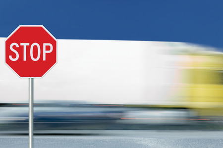 zoned: Red stop road sign, motion blurred truck vehicle traffic in background, regulatory warning signage octagon, white octagonal frame, metallic pole post Stock Photo