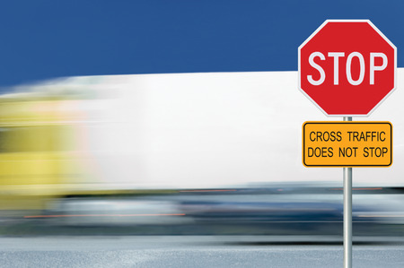 prevent: Red stop road sign, motion blurred truck vehicle traffic in background, regulatory warning signage octagon, white octagonal frame, metallic pole post, yellow cross traffic does not stop text signage Stock Photo