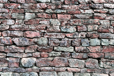 calcium carbonate: Stone wall closeup, horizontal stonewall pattern background, old aged weathered red and grey grunge limestone dolomite calcium carbonate hard sedimentary slate slab rock texture, natural grungy textured bricks, beige, yellow, reddish, gray brick vintage Stock Photo