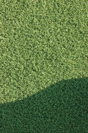 pasto sintetico: Artificial grass fake turf synthetic lawn field macro closeup with gentle shaded shadow area, green sports texture background with a shade