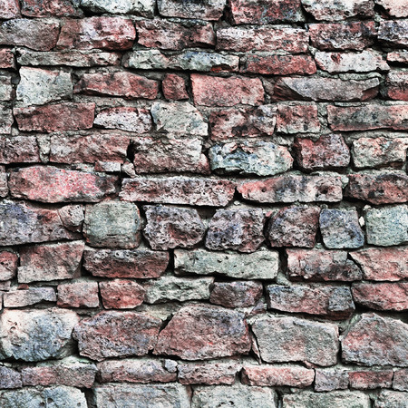 calcium carbonate: Stone wall closeup, stonewall pattern background, old aged weathered red and grey grunge limestone dolomite calcium carbonate hard sedimentary slate slab rock texture, natural grungy textured bricks, beige, yellow, reddish, gray brick vintage Stock Photo